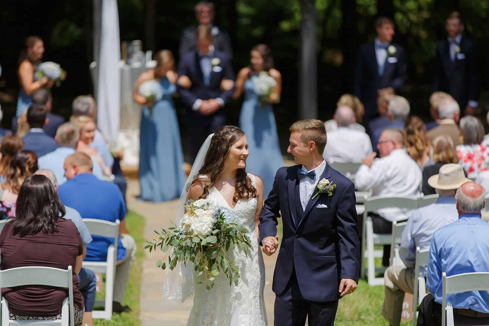 Bride and Groom smiling at each other during recessional at outdoor wedding ceremony