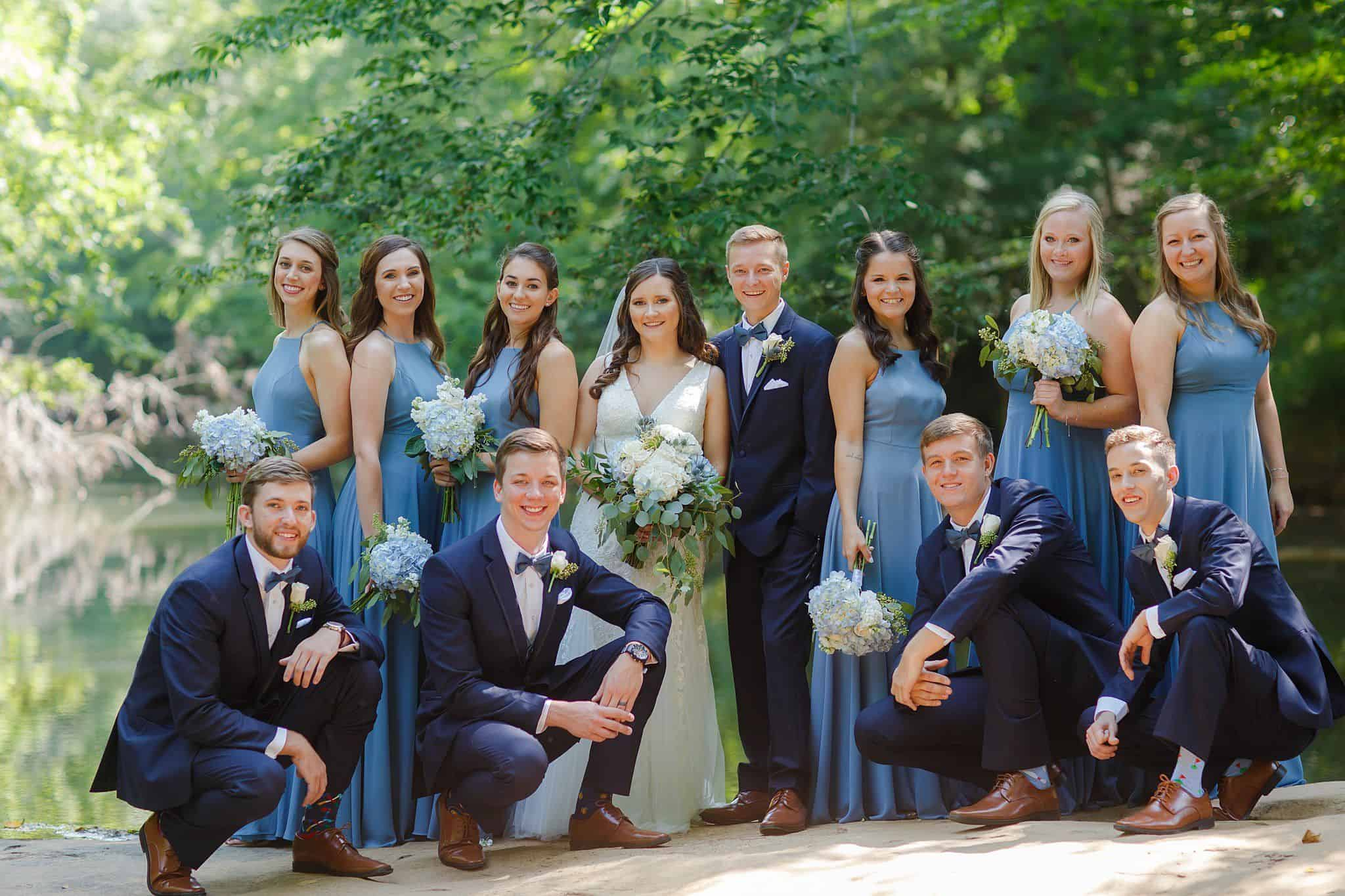 Bridal Party posing outdoors on the river with bride and groom