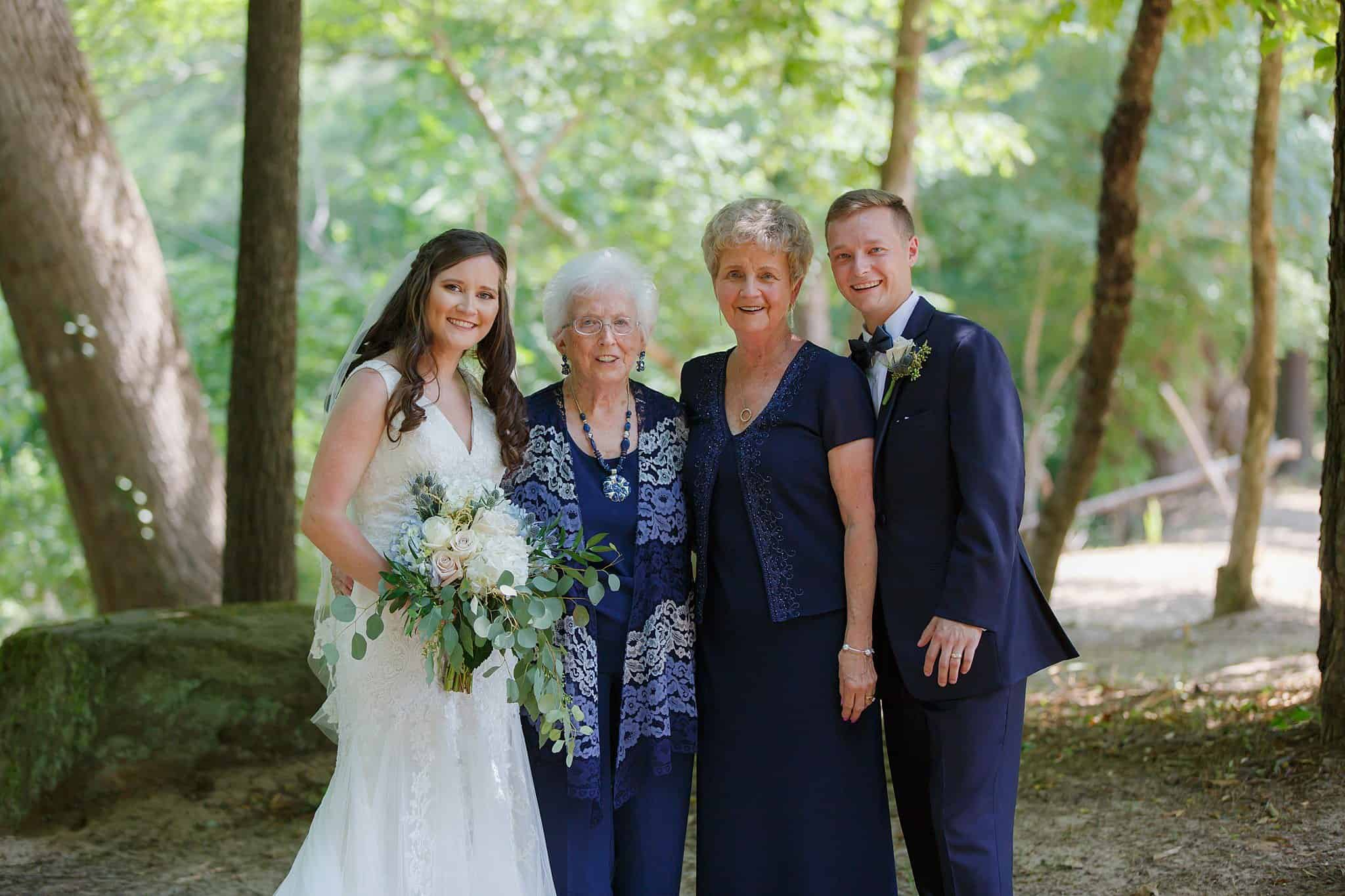 Bride holding bridal bouquet with Groom posing with Grandmothers outside on the river