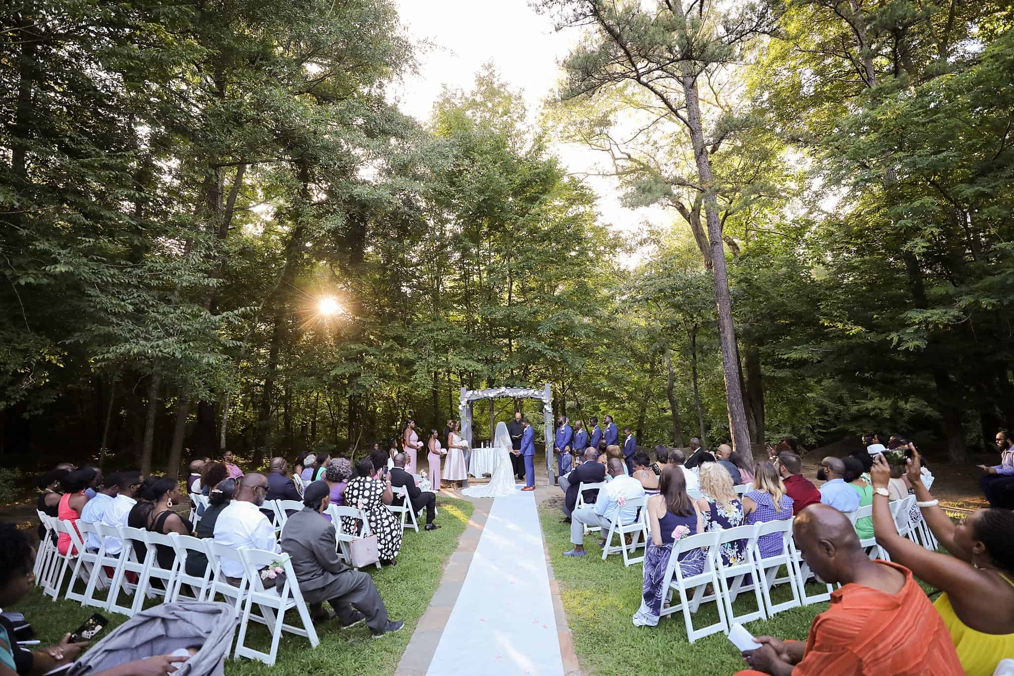 Wedding Ceremony at a river outdoors with bride and groom at altar in front of wedding guests seated in white folding chairs