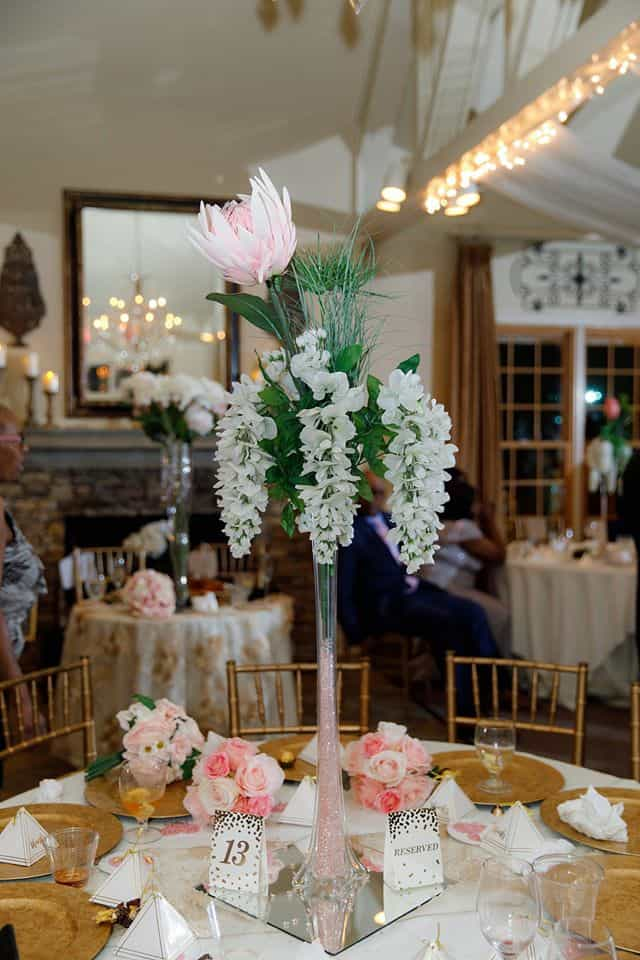 Tall Centerpiece on Guest Table at Wedding Reception with White and Pink Silk Flowers with Gold Chargers at Placesetting and Wedding Favor
