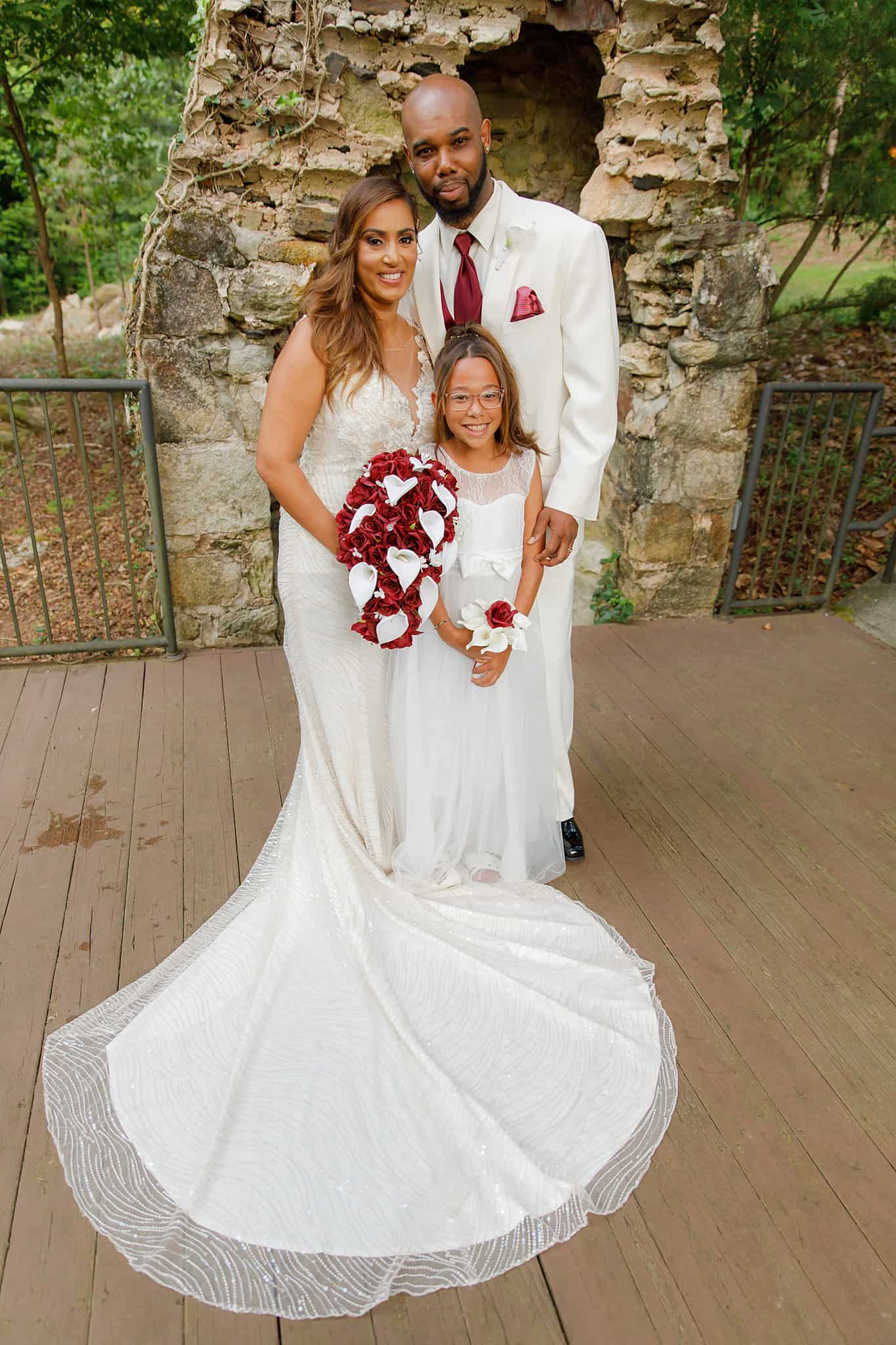bride and groom pose with daughter flowergirl