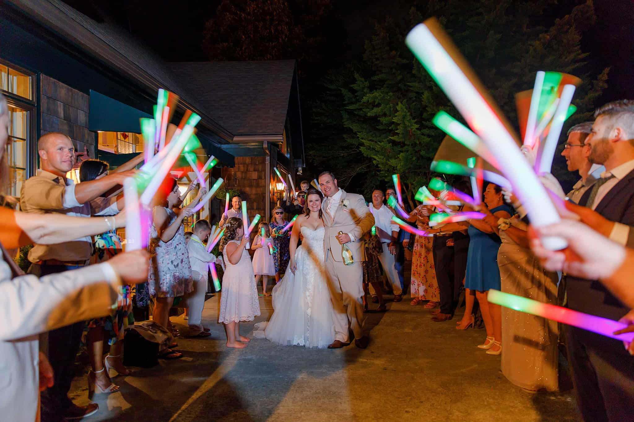 Bride and Groom departing wedding at night with guests holding brightly colored glowsticks