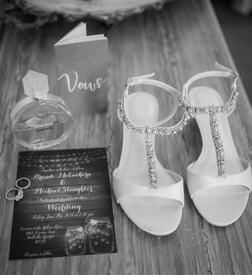 Strappy Sandals bejeweled with Chanel Parfume, Wedding Band, Engagement Ring, Wedding Vows, Wedding Invitation displayed on table