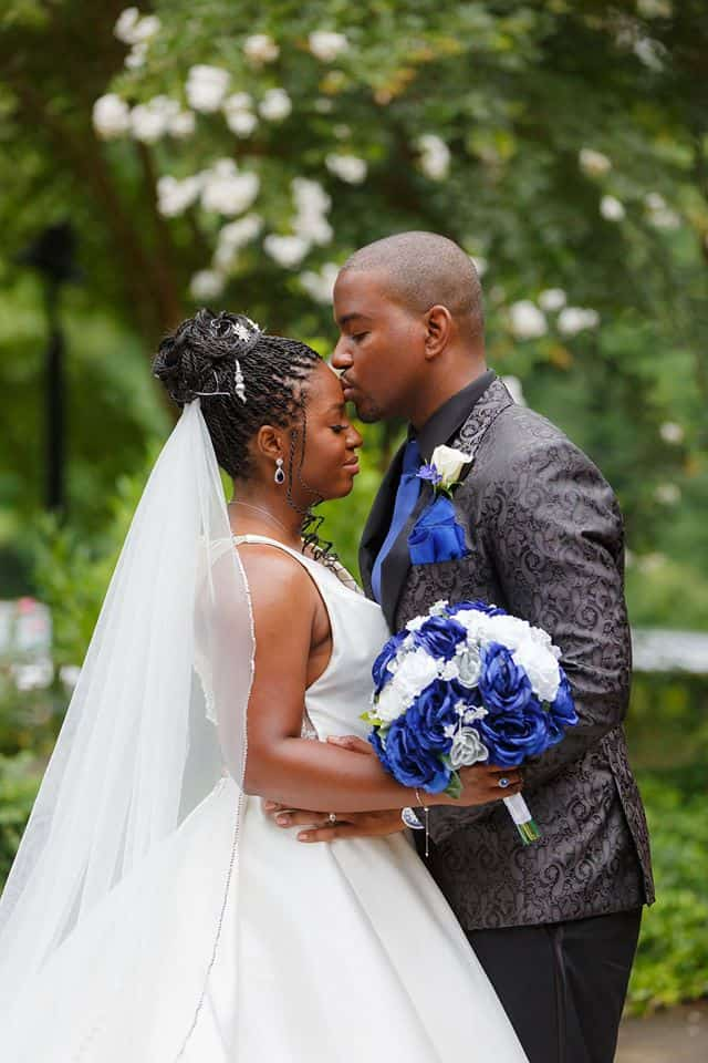 Groom kissing Bride on forehead outdoors holding bridal bouquet