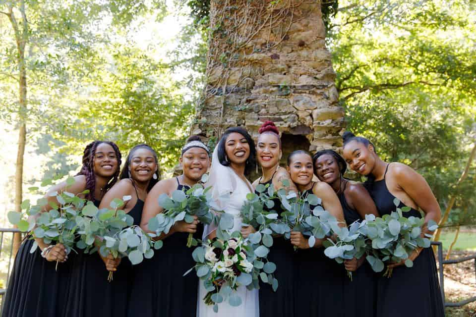Bride with bridesmaids outdoors in front of chimney carrying bouquets of eucalyptus