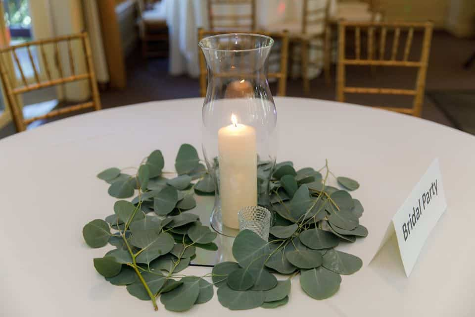 Guest Table at Wedding w/ Hurrican Vase filled w/ White Pillar with Eucalyptus Leaves