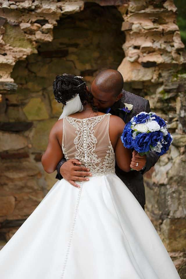Bride and Groom in front of chimney embracing