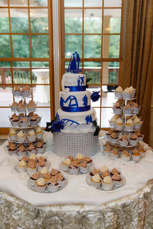 Wedding Cake with blue ribbon with tiers of cupcakes on stands and cupcakes on plates