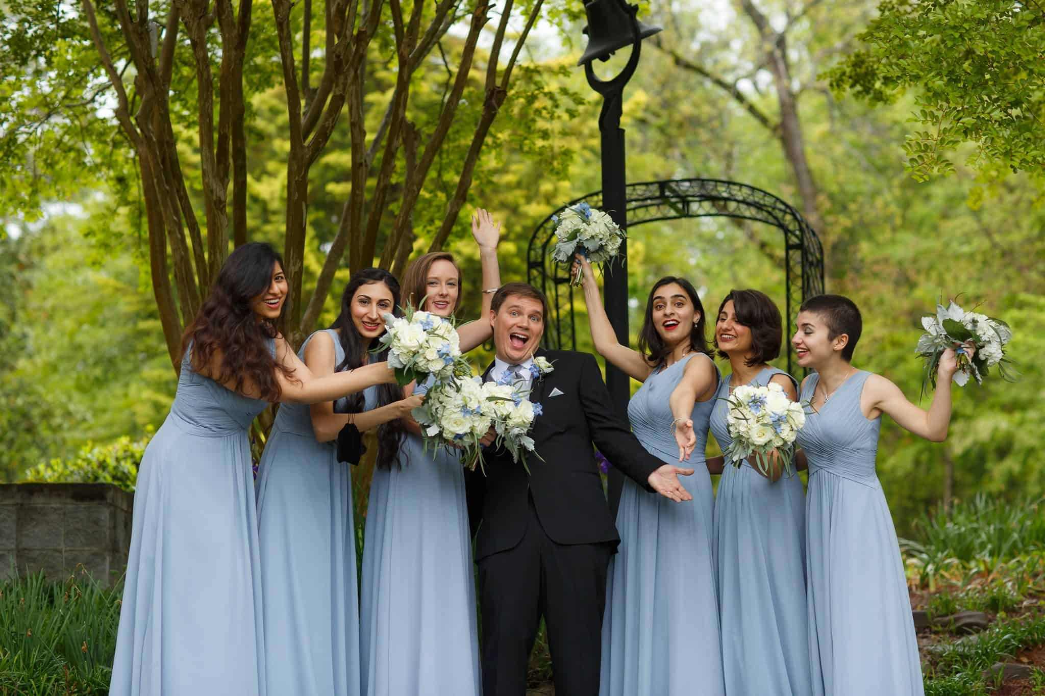 Bridesmaids in blue bridesmaids dresses holding bouquets in ivory and blue with groom in the center