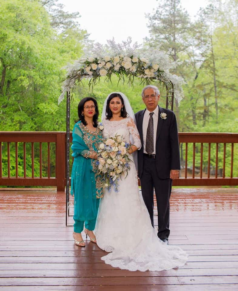 Bride with parents on deck holding beautiful cascading bridal bouquet in ivory, blush and blue