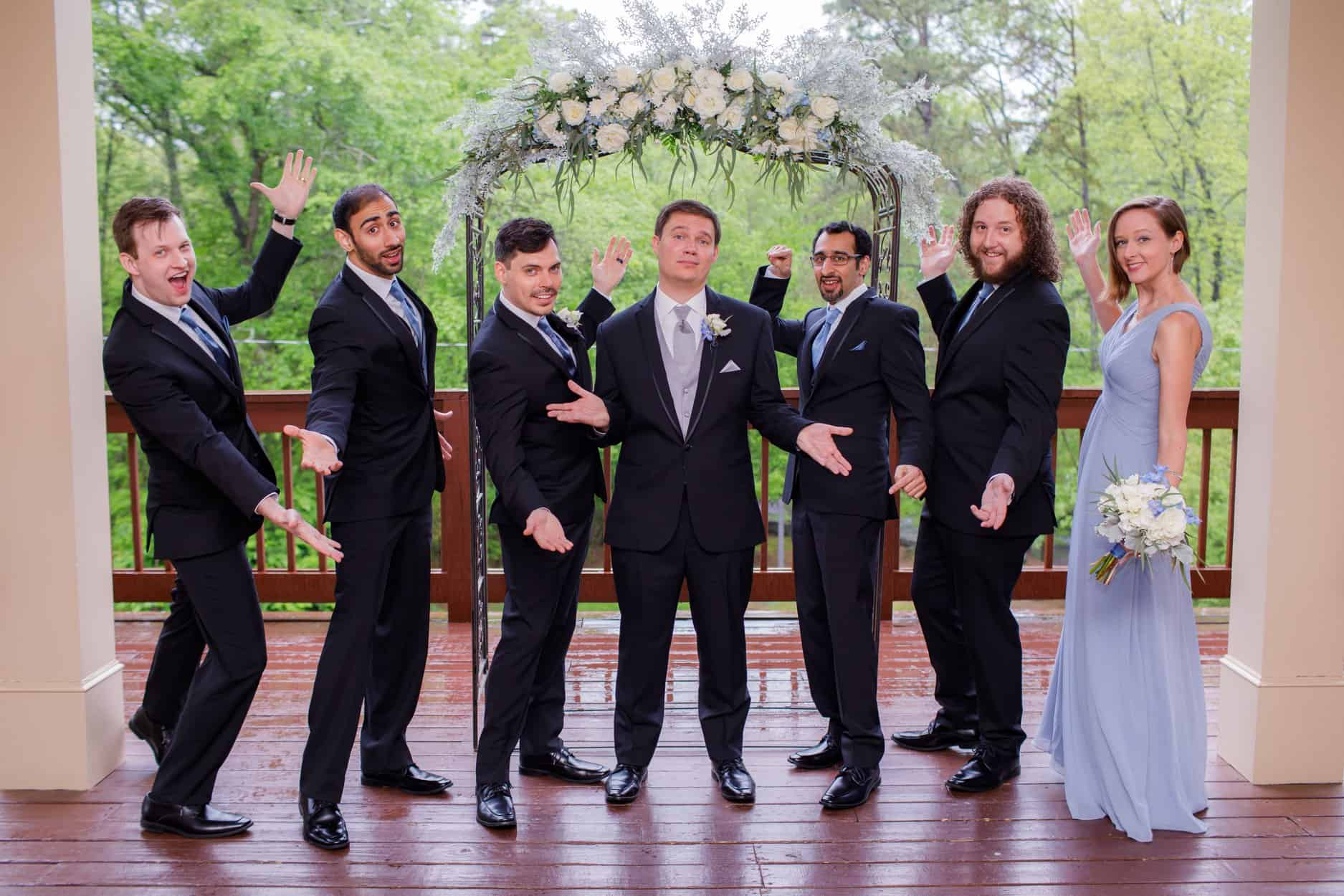 Groom with groomsmen and groomsmaid on deck at ceremony altar with large floral arrangement in ivory, gray, blue