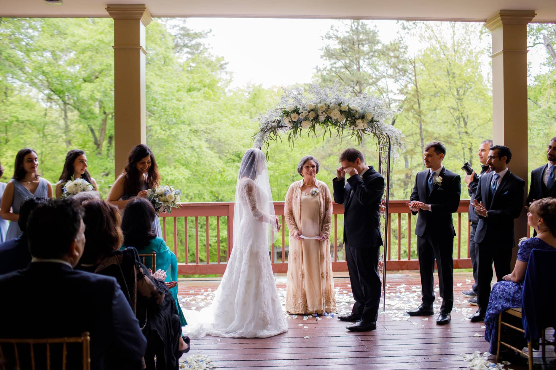 Emotional Groom at altar under arbor with bride, officiant and bridal party