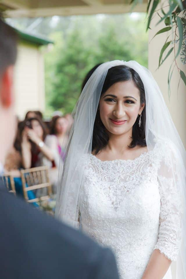 Bride smiling at Groom in beautiful lace wedidng gown and long veil during wedding ceremony at the altar outside on a deck