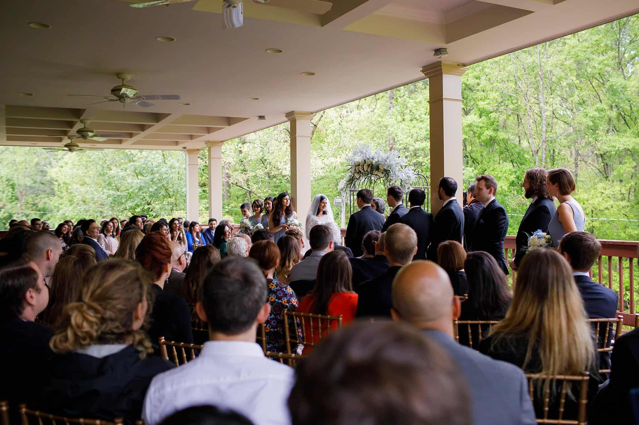 Wedding Ceremony on Deck with Bridal Party, Bride and Groom at Altar under Arbor decorated with florals in ivory, blush, blue