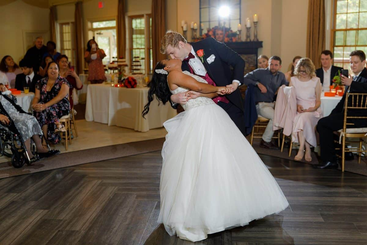 Groom tilts bride back for a kiss during first dance