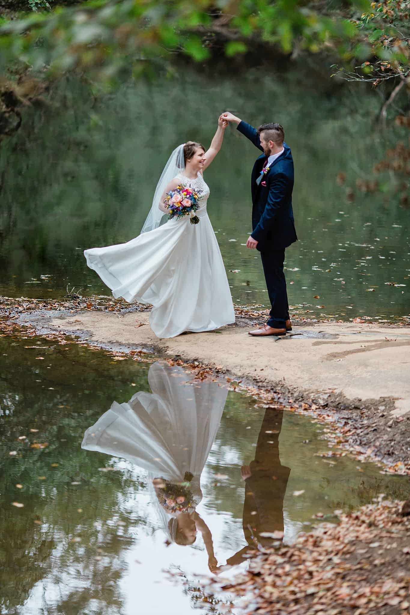 Bride twirls with groom down by the river