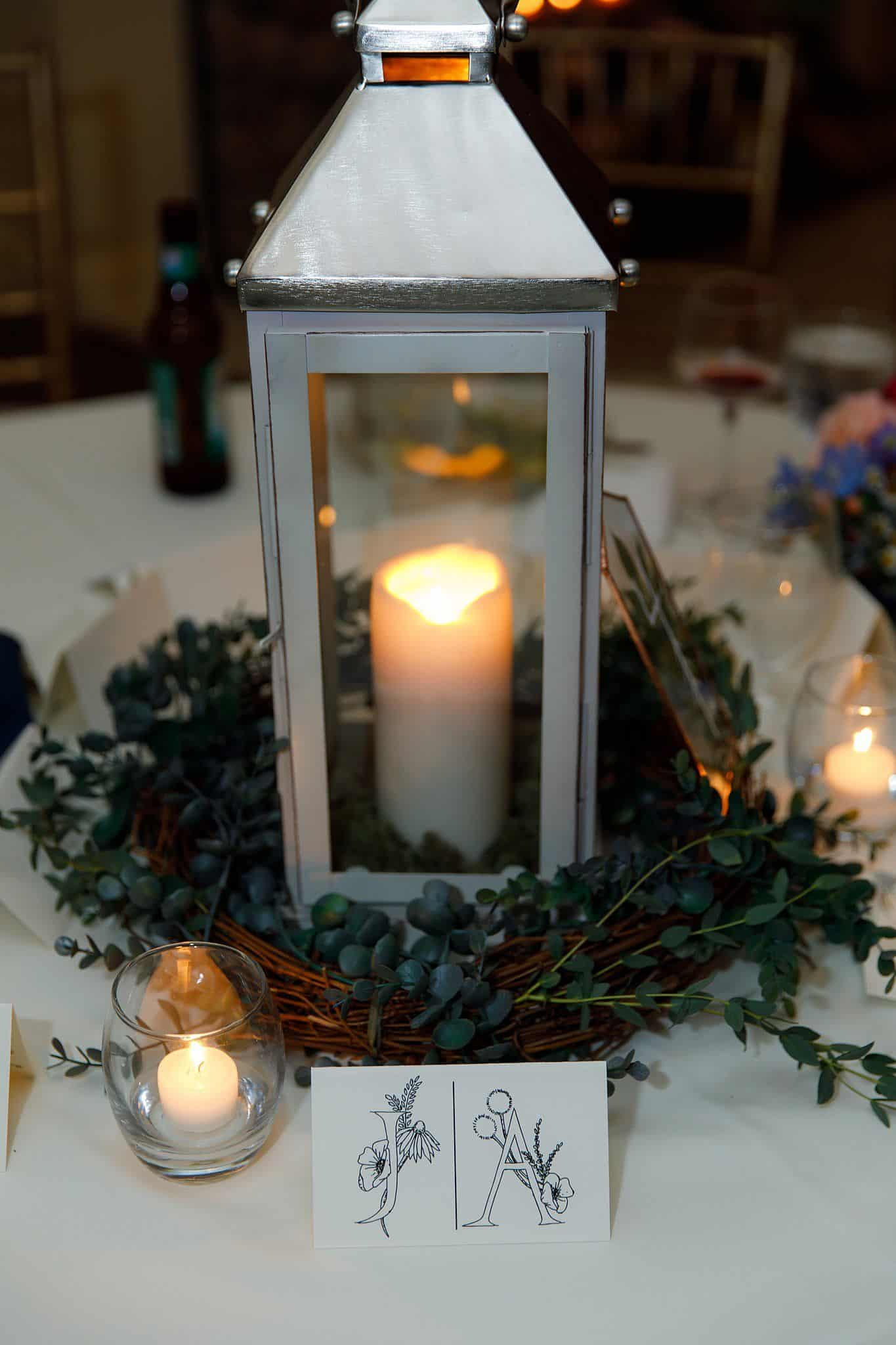 White lanterns with greenery and candles