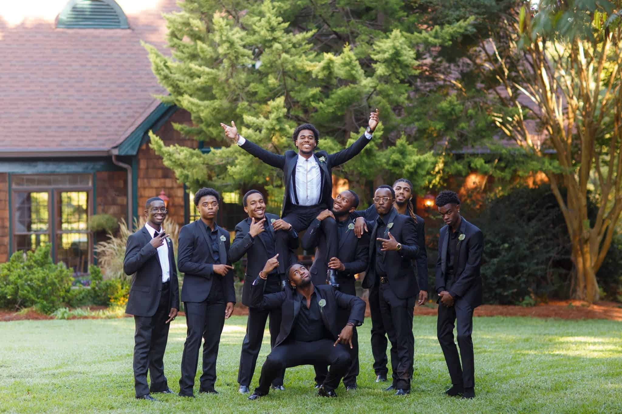 Groom on shoulders of 2 groomsmen with others around him outside in black