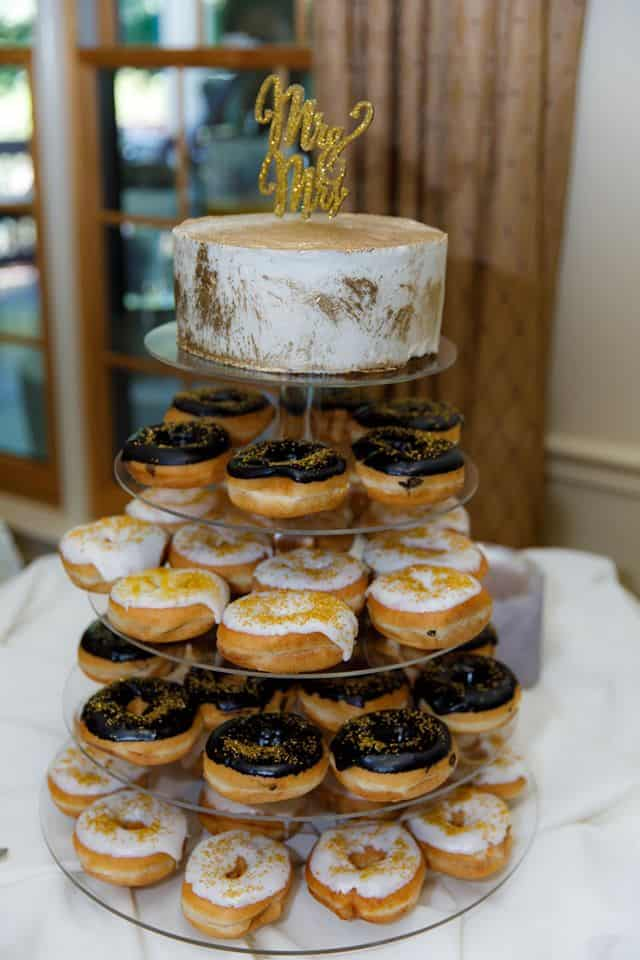 One Tier Wedding Cake Dusted in Gold with Gold Topper and 4 Tiers of Doughnuts Below